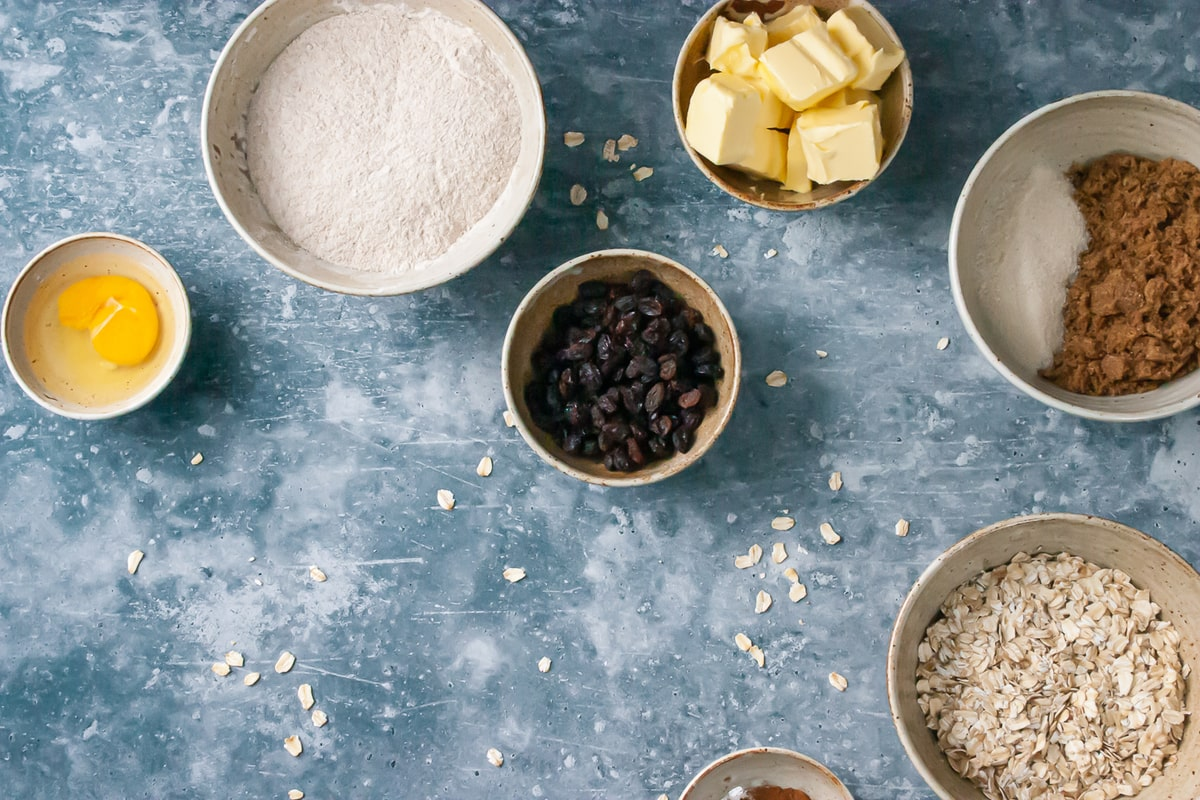 Ingredients for oatmeal raisin cookies in separate bowls