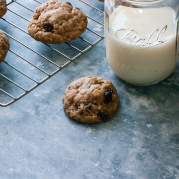 Oatmeal Raisin Cookies on a Baking Rack with a Glass of Milk on the Side