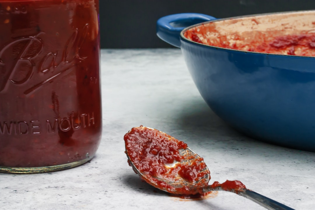 sauce on a spoon surrounded by Braiser pan and mason jar with a black background
