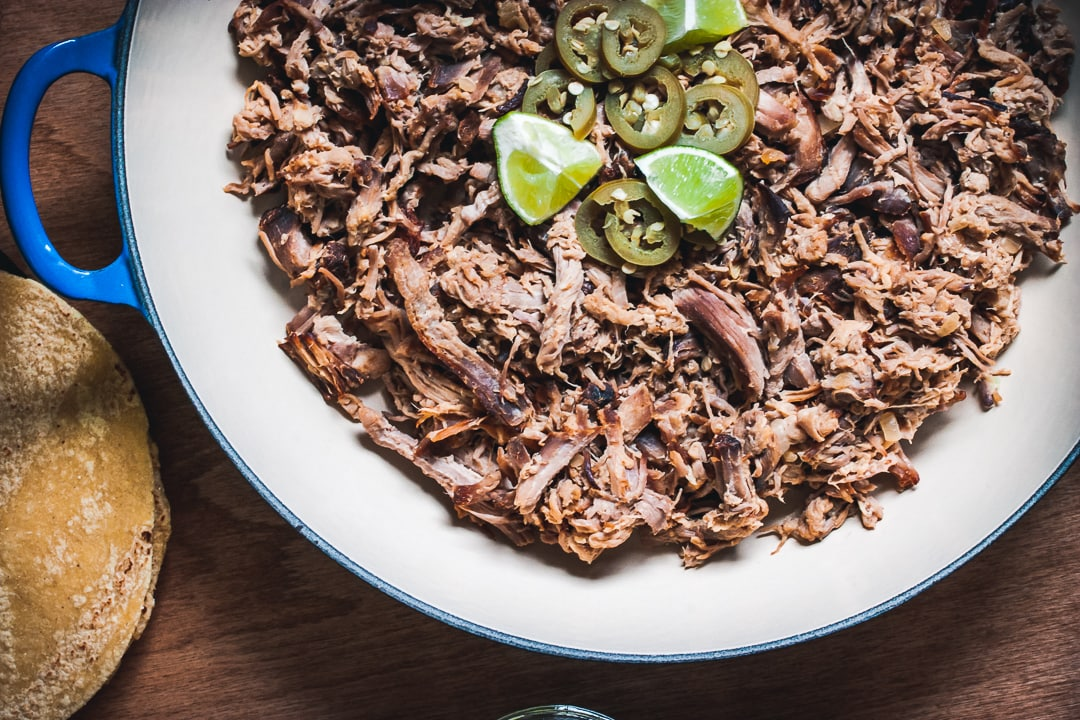 citrus pulled pork shredded in a braiser pan with limes and jalapeños on top