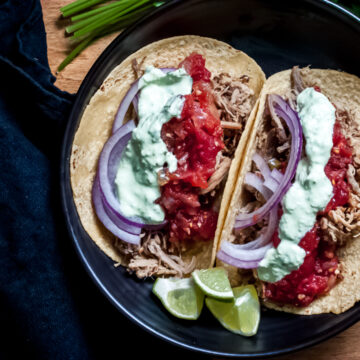 2 assembled citrus pulled pork tacos in a black bowl surrounded by cilantro and and napkin