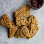 Buttermilk scones stacked on top of one another with a jar of jam and a spreader