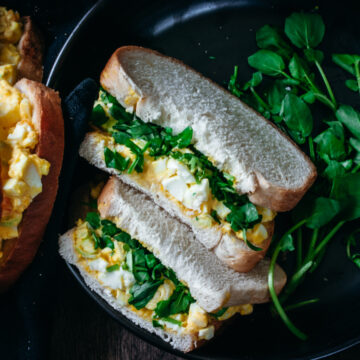 egg salad sandwich with watercress in a bowl with a second sandwich on the side
