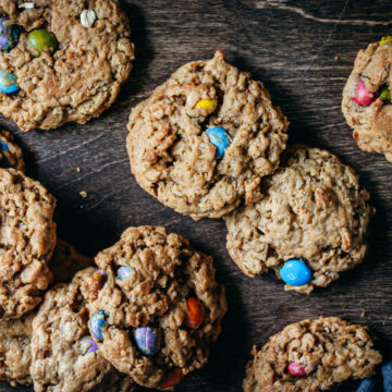 Baked Monster Cookies layered together on a dark wood background