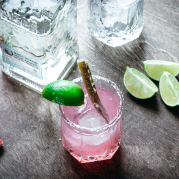 A Rhubarb Margarita with tequila, limes, and a glass filled with ice on the side