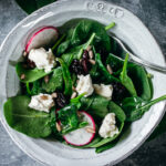 Simple Spinach Salad in a white bowl with a fork
