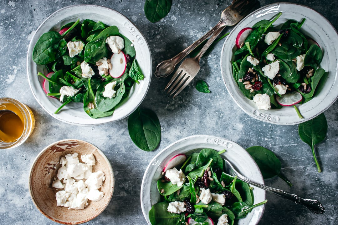 Salad in 3 white bowls with goat cheese and forks on the side