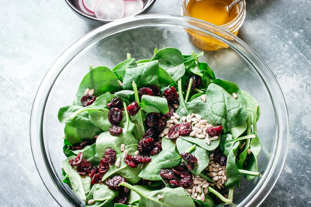 spinach, cranberries, and sunflower seeds in a glass bowl