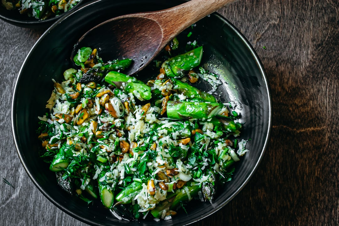 Finished Stove Top Asparagus with pistachios and herbs in a black serving bowl with a spoon