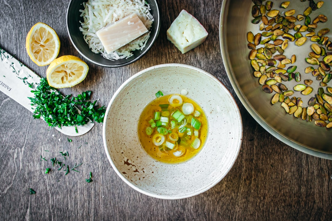 green onions and olive oil mixed in a bowl surrounded by cheese, lemons, herbs, and pistachios