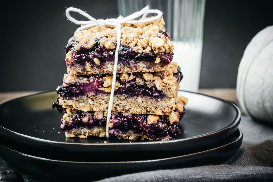 kitchen twine wrapped around 3 berry crumble bars stacked on top of the other