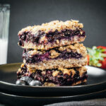 3 bars stacked on top of one another with a glass of milk and berries on the side