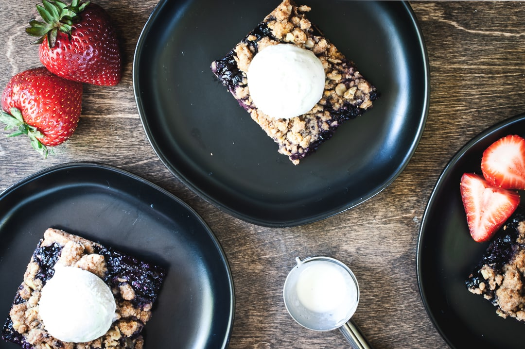 3 berry crumble bars on 3 plates topped with ice cream and strawberries on the side