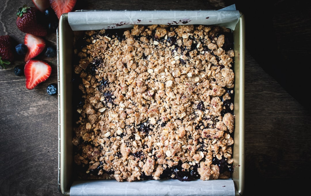 assembled berry crumble in a baking pan ready to be put in the oven