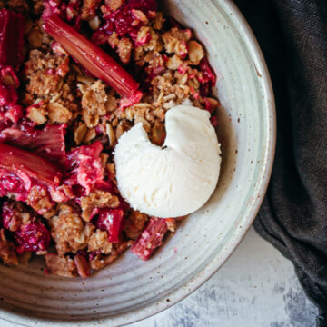 Rhubarb crisp in a bowl topped with ice cream with a napkin on the side