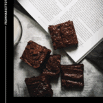 rye brownies on a magazine with a napkin and a glass of milk on the side