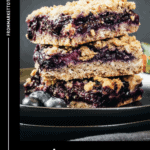 3 berry crumble bars stacked on top of one another with a glass of milk and strawberries and blueberries on the side