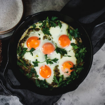 pesto eggs in a skillet with plates and a napkin on the side