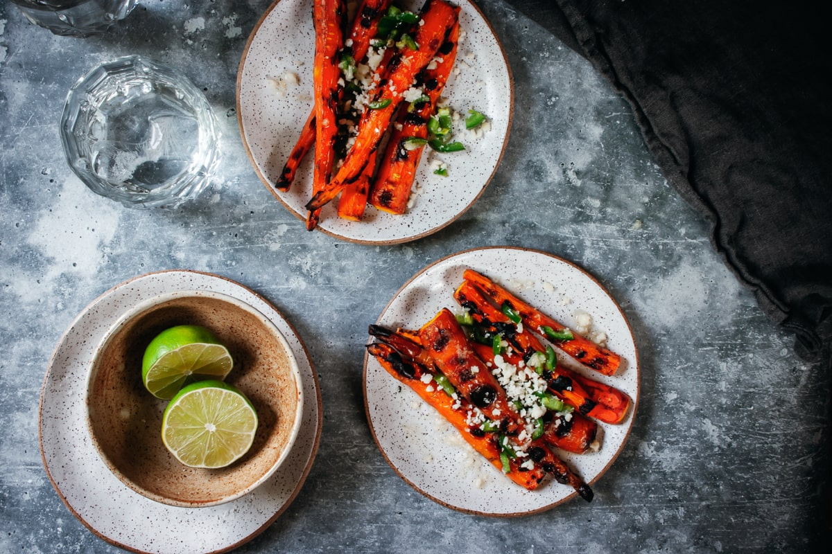 grilled carrots with jalapeño, lime, and cotija cheese on 2 plates with a water glass on the side