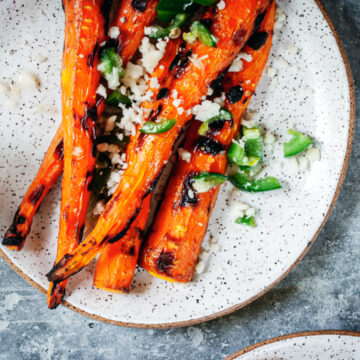 grilled carrots with jalapeño, lime, and cotija cheese on a white plate