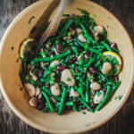 3-bean salad with lemon and dill in a yellow serving bowl with a wooden spoon