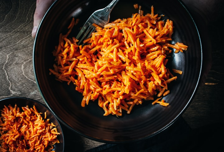 shredded carrot salad in a bowl with a fork on the side