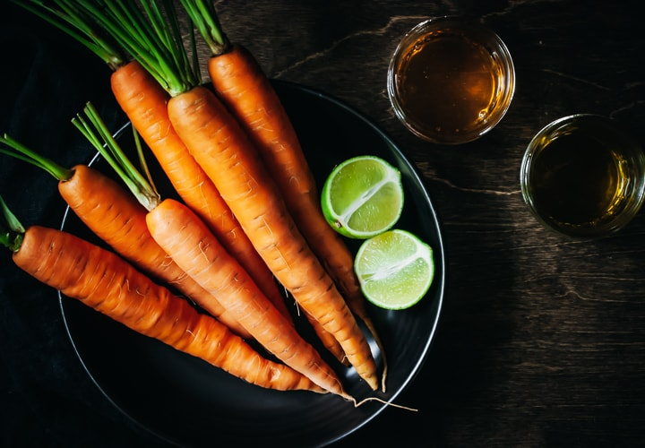 carrots, limes, honey, and olive oil in different size bowls