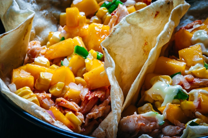 Baked fish tacos topped with peach and jalapeño salsa and Mexican crema