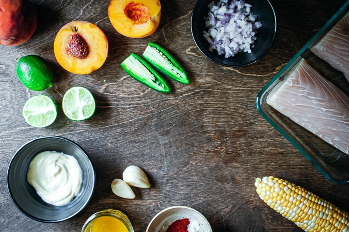 Ingredients for baked fish tacos with peach, corn, and jalapeño salsa arranged in a circle on a wood background