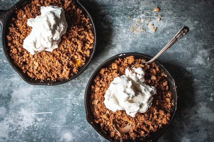 peach crumble for two in two cast iron skillets topped with whipped cream and two spoons on the side