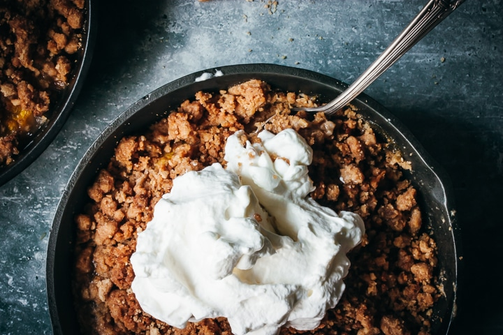 peach crumble for two in a cast iron skillet topped with whipped cream and two spoons on the side