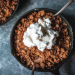 peach crumble for two in a cast iron skillet topped with whipped cream and two spoons
