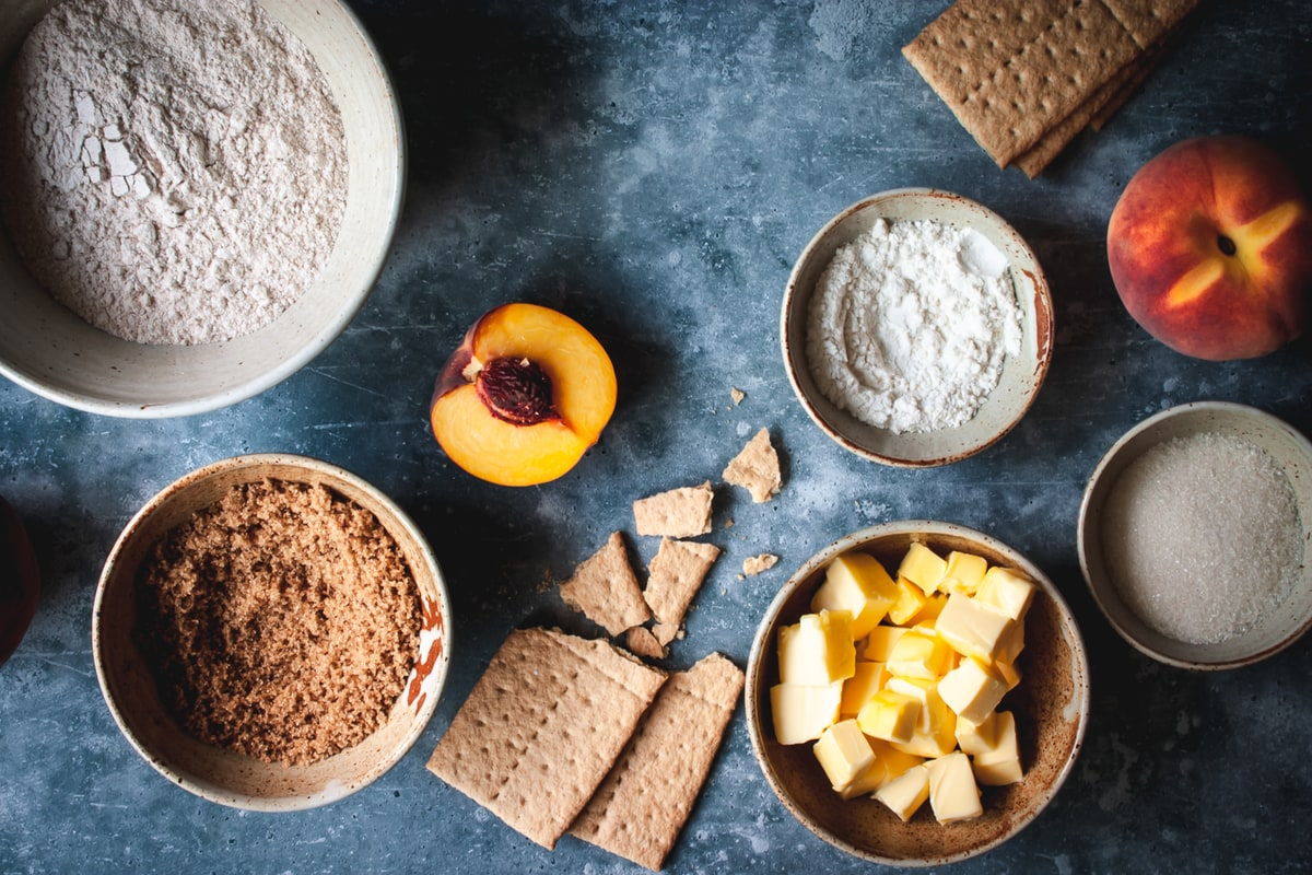 ingredients in different size white bowls with graham crackers and peaches on the side