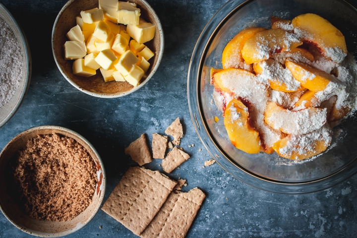 peaches with arrowroot powder and sugar in a bowl with butter and sugar on the side