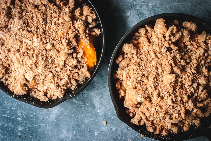 two cast iron skillets filled with peach crumble and ready to be baked