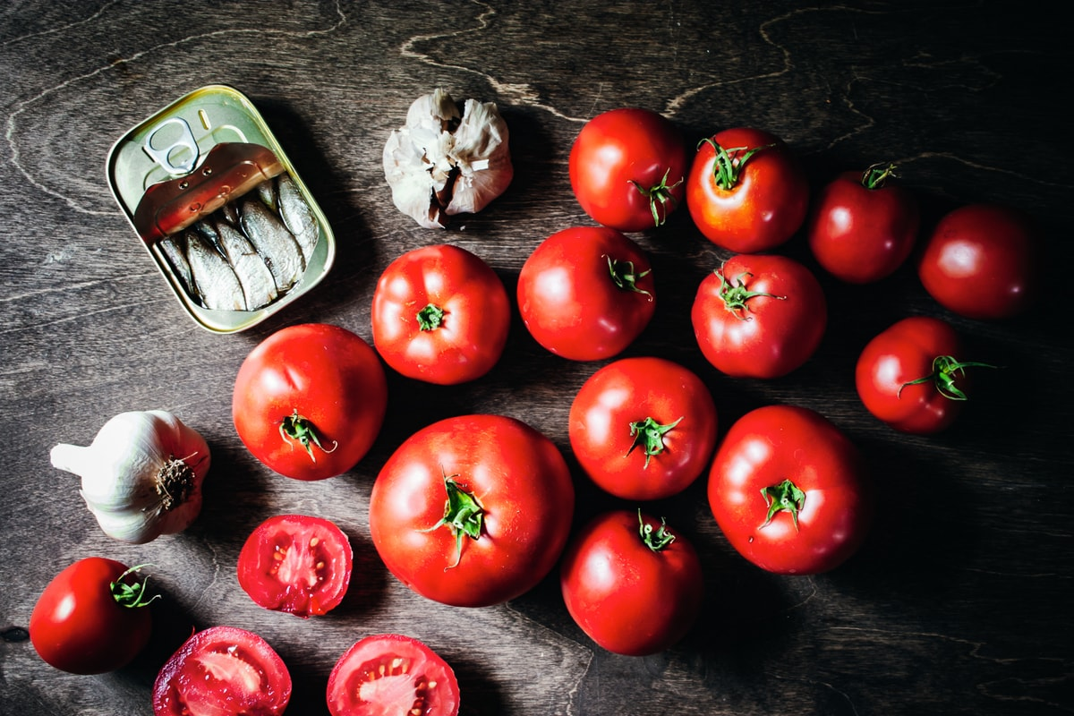 tomatoes, garlic, and sardines on a wood background