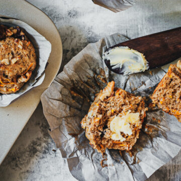 a whole wheat carrot muffin cut in half with a pad of butter on top and a spreader on the side