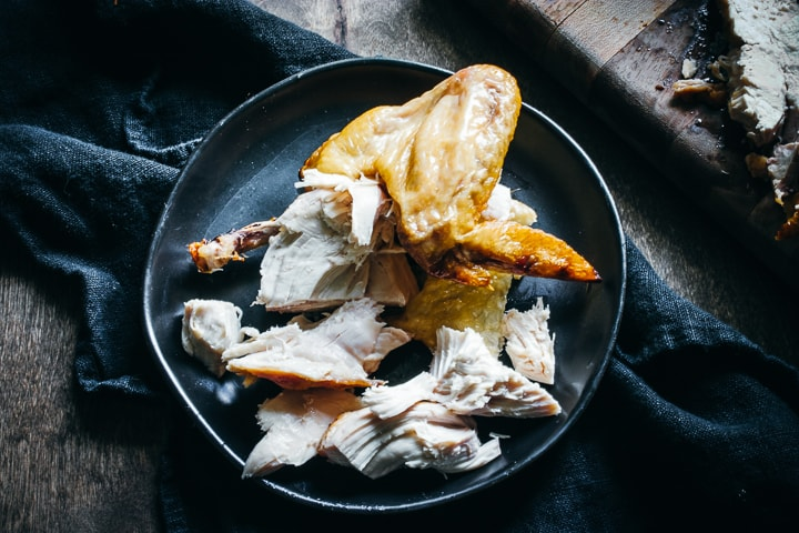shredded chicken leg on plate with a napkin on the side