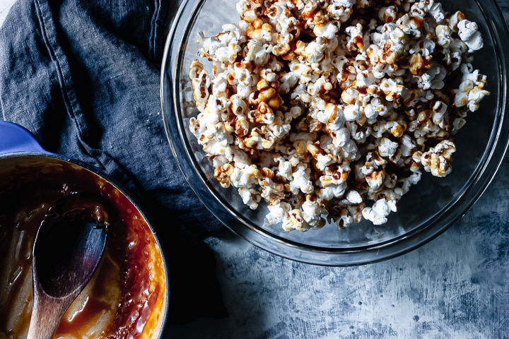 homemade salted caramel popcorn in a glass bowl with a pot full of caramel on the side